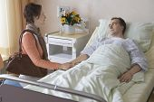Side view of a woman visiting man in hospital