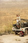 picture of four-wheel drive  - Middle aged couple standing in back of four - JPG