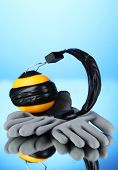 Protective gloves and headphones on blue background