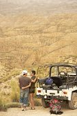 image of four-wheel drive  - Rear view of affectionate couple looking at desert from cliff standing by four - JPG
