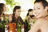 foto of jug  - Portrait of happy young woman enjoying red wine with friends in background - JPG