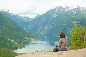 picture of fjord  - Young girl working on a laptop at a cliff edge - JPG