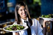pic of restaurant  - Hispanic waitress serving two plates of salad in a restaurant - JPG
