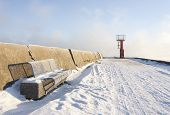 foto of boggy  - Blue metal bench on snowy mole and small beacon or lighthouse at the end of the pier - JPG
