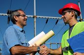 pic of substation  - Smiling workers with blueprints and clipboard in meeting at electrical substation - JPG