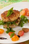 stock photo of crab-cakes  - Two crab cakes appetizer garnished with spicy sauce green salad and raspbery.