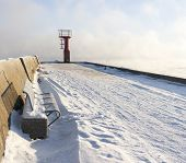 picture of boggy  - Blue metal bench on snowy mole and small beacon or lighthouse at the end of the pier - JPG