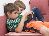 stock photo of indoor games  - boys playing video games on the tablet computers - JPG
