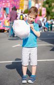 stock photo of candy cotton  - Portrait of cute child eating cotton candy over a summer fair festival background - JPG