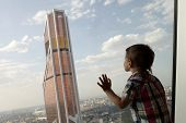 stock photo of penthouse  - Child looking at skyscrapers from penthouse in Moscow - JPG