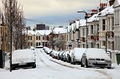stock photo of slippery-roads  - Snow cityscape of a terraced street in London England with slippery blizzard conditions showing cars covered with ice and snow - JPG
