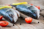 foto of bass fish  - Two raw seabass fish with cherry tomatoes on a rustic wooden background