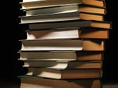 Pile of hardcover books stacked on top of one another in a shadowy room on a wooden desk with copyspace in the foreground poster