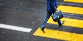 stock photo of pedestrian crossing  - Man rushing over a road crossing in a city on a rainy day  - JPG