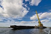 picture of barge  - Port crane unloads a barge with sand - JPG