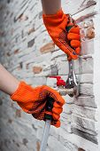 stock photo of adjustable-spanner  - Closeup portrait of plumbers hands  in orange gloves a flexible pipe to a tap with adjustable spanner monkey wrench on grey stone wall - JPG