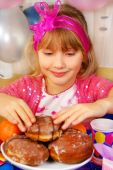 Young Girl Eating Donuts On Party