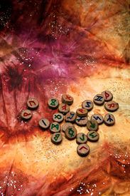 stock photo of rune  - hand carved and painted wooden runes an ancient alphabet known as the futhark are on a colorful hand dyed fabric with small sparkling beads - JPG