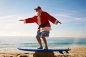 picture of christmas claus  - Santa Claus practices his Surfing Skills on his Surf Board on the beach - JPG