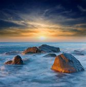 pic of promontory  - Sunset on sea shore with stones in water - JPG