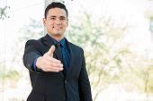 picture of laws-of-attraction  - Attractive Hispanic businessman extending his hand for a handshake and smiling - JPG