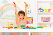 stock photo of adjustable-spanner  - Cute Caucasian little preschool boy sitting by the table with adjustable wrench and regular wrench lifting them up and cheering in room setup - JPG