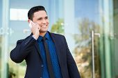 picture of laws-of-attraction  - Attractive Latin businessman using his mobile phone to talk to his clients at work - JPG