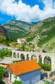 picture of aqueduct  - The colorful houses surround the stone aqueduct in the narrow mountain valley Stari Bar Montenegro - JPG