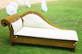 stock photo of lawn chair  - close up shot of wicker chaise lounge on a green lawn - JPG