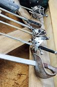 picture of rapier  - Row of six hilts of rapiers on wooden boards and sand - JPG