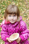 stock photo of face-fungus  - Little beautiful girl in pink holds mushroom and looks at camera at autumn day - JPG