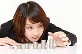 stock photo of japanese coin  - Businesswoman put coins to stack of coins - JPG