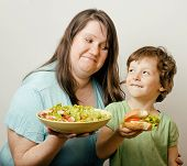 foto of tease  - fat woman holding salad and little cute boy with hamburger teasing real family - JPG