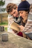 stock photo of under sea  - Closeup of young beautiful couple under blanket reading book in a cold day with sea and dark cloudy sky on the background - JPG