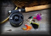picture of fly rod  - Close up top view of fishing fly reel landing net creel and assorted flies partial cork handled pole on rustic wooden boards with vignette border - JPG