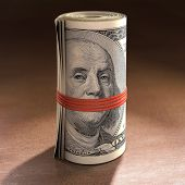 picture of gag  - Money roll with elastic gagging the mouth of Benjamin Franklin - JPG