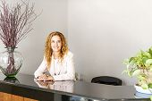 pic of receptionist  - Receptionist standing at reception counter in office - JPG