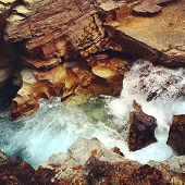stock photo of gushing  - Gushing river falling down through rocks and slowly carving out its path - JPG