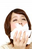 picture of sneezing  - young woman with a allergy sneezing into tissue - JPG