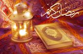 picture of quran  - A beautiful image of Ramadan lantern beside Quran with golden rays over the image - JPG