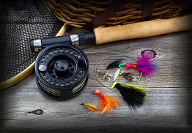 stock photo of fly rod  - Close up top view of fishing fly reel landing net creel and assorted flies partial cork handled pole on rustic wooden boards with vignette border - JPG