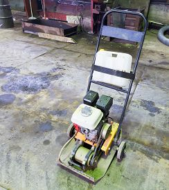 image of vibration plate  - small gasoline single direction plate compactor on concrete road - JPG