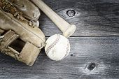 stock photo of baseball bat  - Vintage concept of old worn glove bat and used baseball on rustic wood - JPG