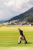 image of golf bag  - a golf player playing on a beautiful golf course and a golf bag full of golf clubs - JPG