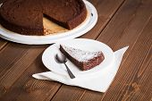 stock photo of time-piece  - Homemade chocolate blackout cake with a cut piece on a dark wooden table  - JPG