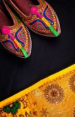 foto of flea  - Colorful ethnic shoes and yellow Rajasthan cushion cover on flea market in India - JPG