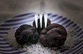 picture of truffle  - Three fresh mushrooms black truffle with a fork on a plate - JPG