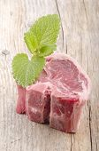 picture of lamb chops  - raw lamb chop with mint on rustic wooden table - JPG