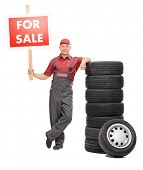 picture of piles  - Full length portrait of a cheerful male mechanic standing by a pile of tires and holding a big red for sale sign isolated on white background - JPG