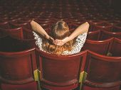 image of cinema auditorium  - Rear view shot of a young woman sitting alone in an auditorium - JPG